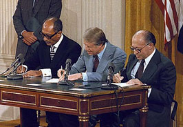 President Jimmy Carter and leaders of Egypt and Israel signing documents