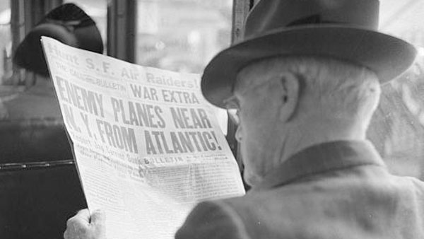 "a photograph of a man reading a 1941 newspaper with the headline ""Enemy Planes Near N.Y. from Atlantic"""