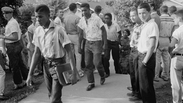 black and white photograph of African-American teenage boys heading to school, while being watched by a group of white teen boys
