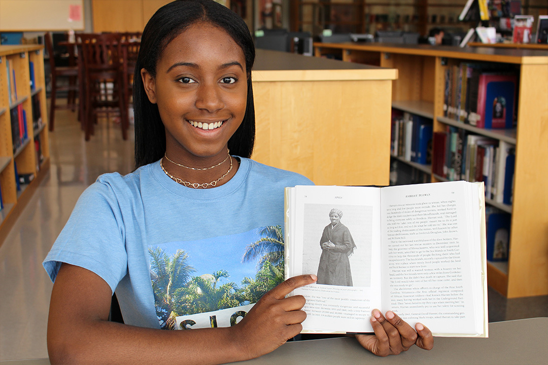 Jasmine sitting in a library pointing to a photo of Harriet Tubman in a book she is holding