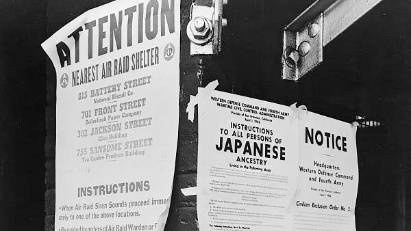 black and white photo of posters displayed on a street corner