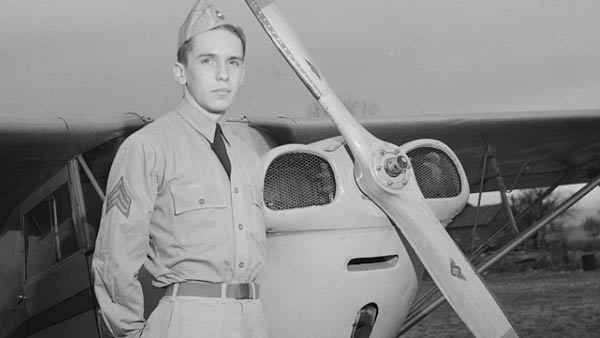 black and white photo of a man in uniform standing in front of a small propeller plane