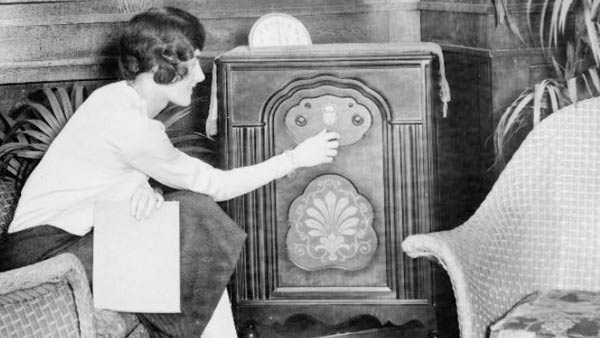 black and white photo of a woman turning on a large radio