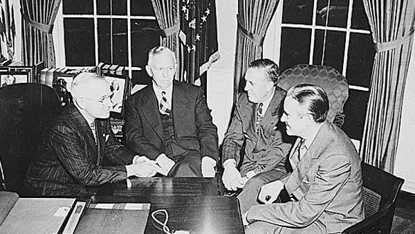 black and white photo of the four men seated by the desk in the oval office