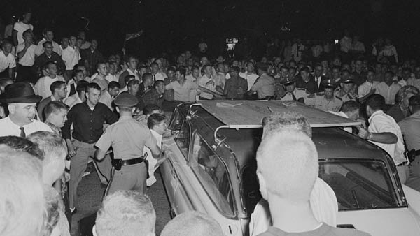 black and white photo of a large mob of people surrounding a car